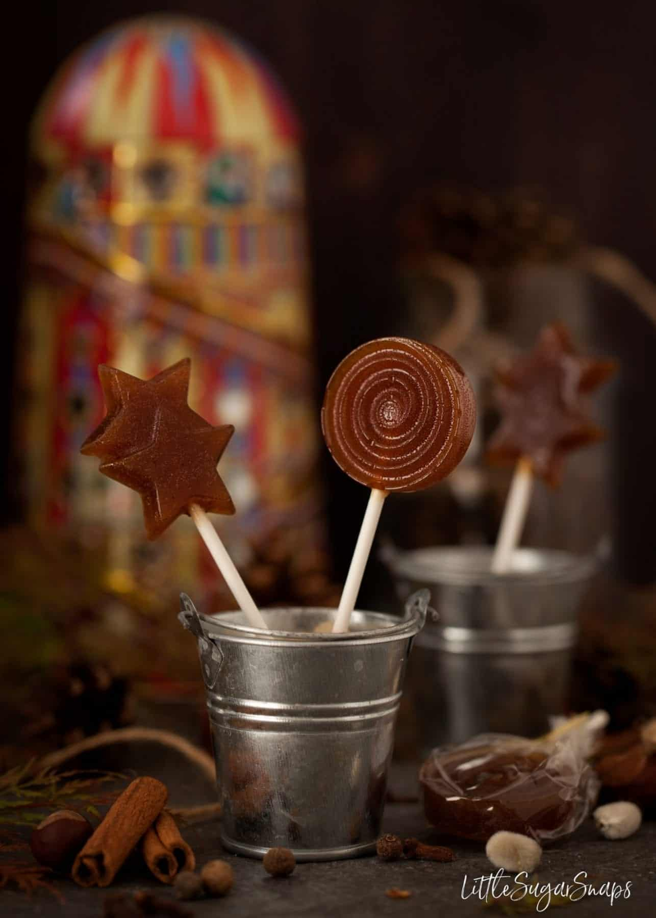 Small metal buckets containing pumpkin spiced toffee lollipops.