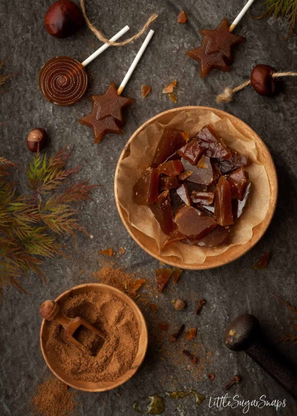 Pumpkin Spiced Toffee pieces in a wooden bowl with lollipops alongside.