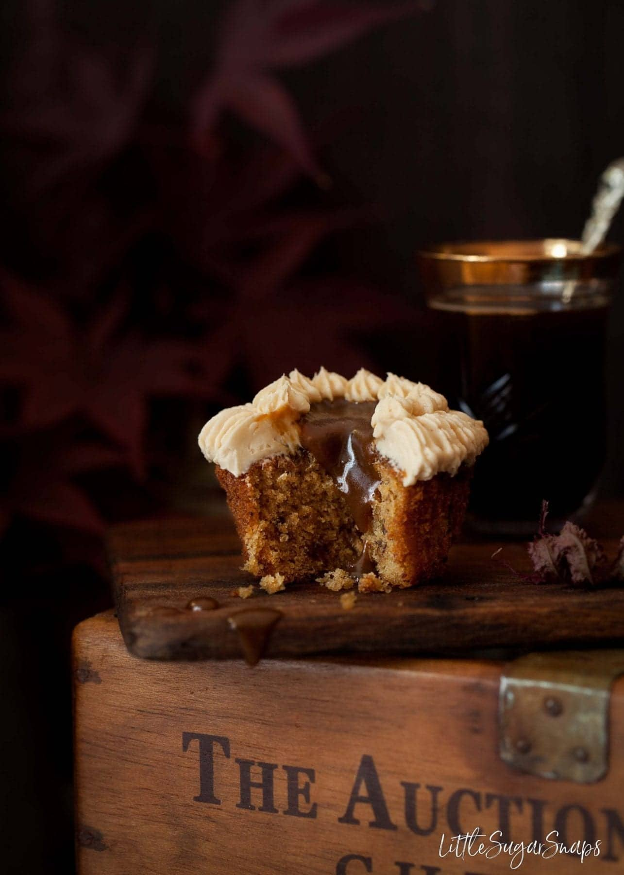 Sticky Toffee Pudding Cupcake cut open with sauce running down the inside. One a wooden board