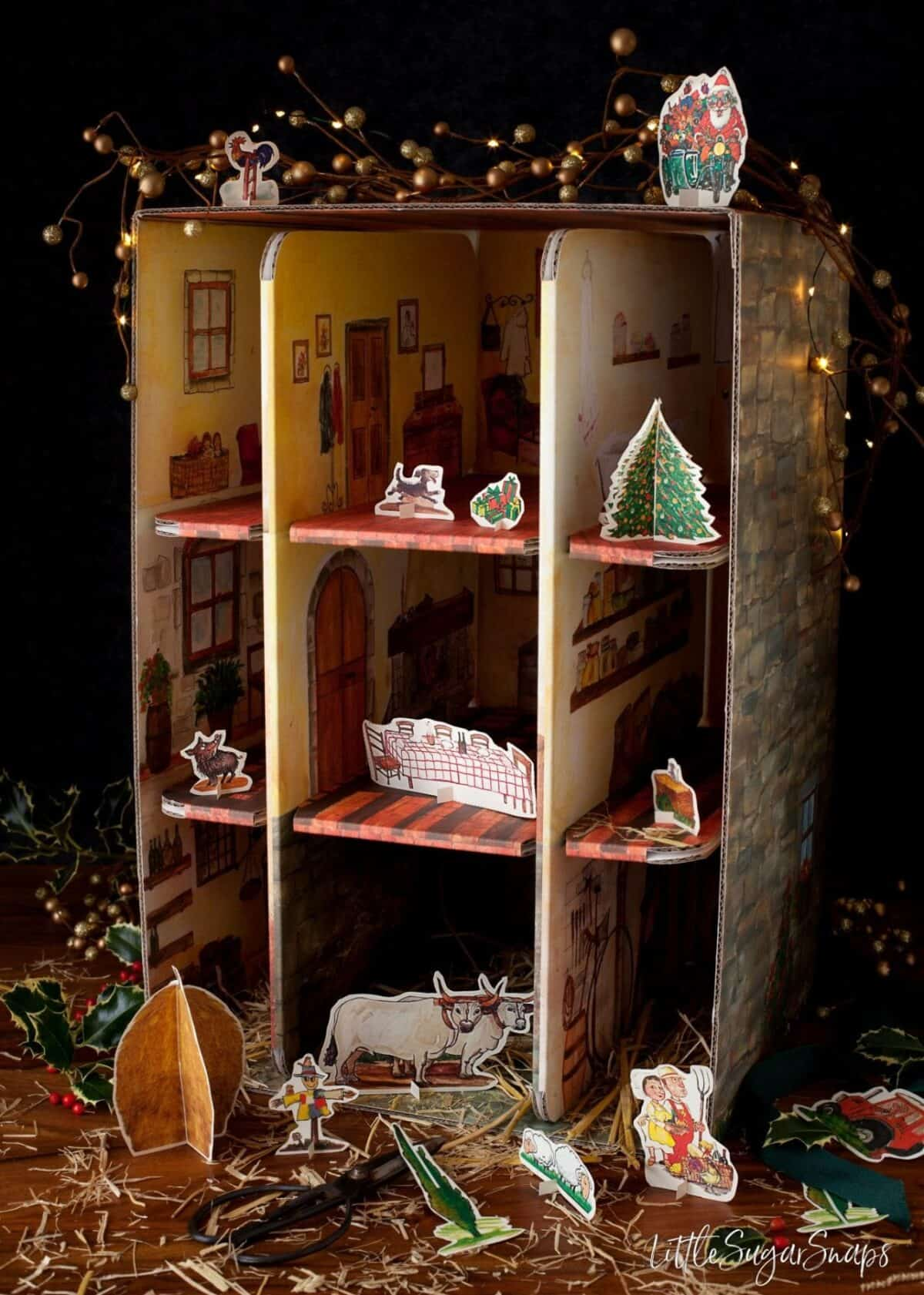 Cardboard toy farmhouse style dolls house with cut out animal figures