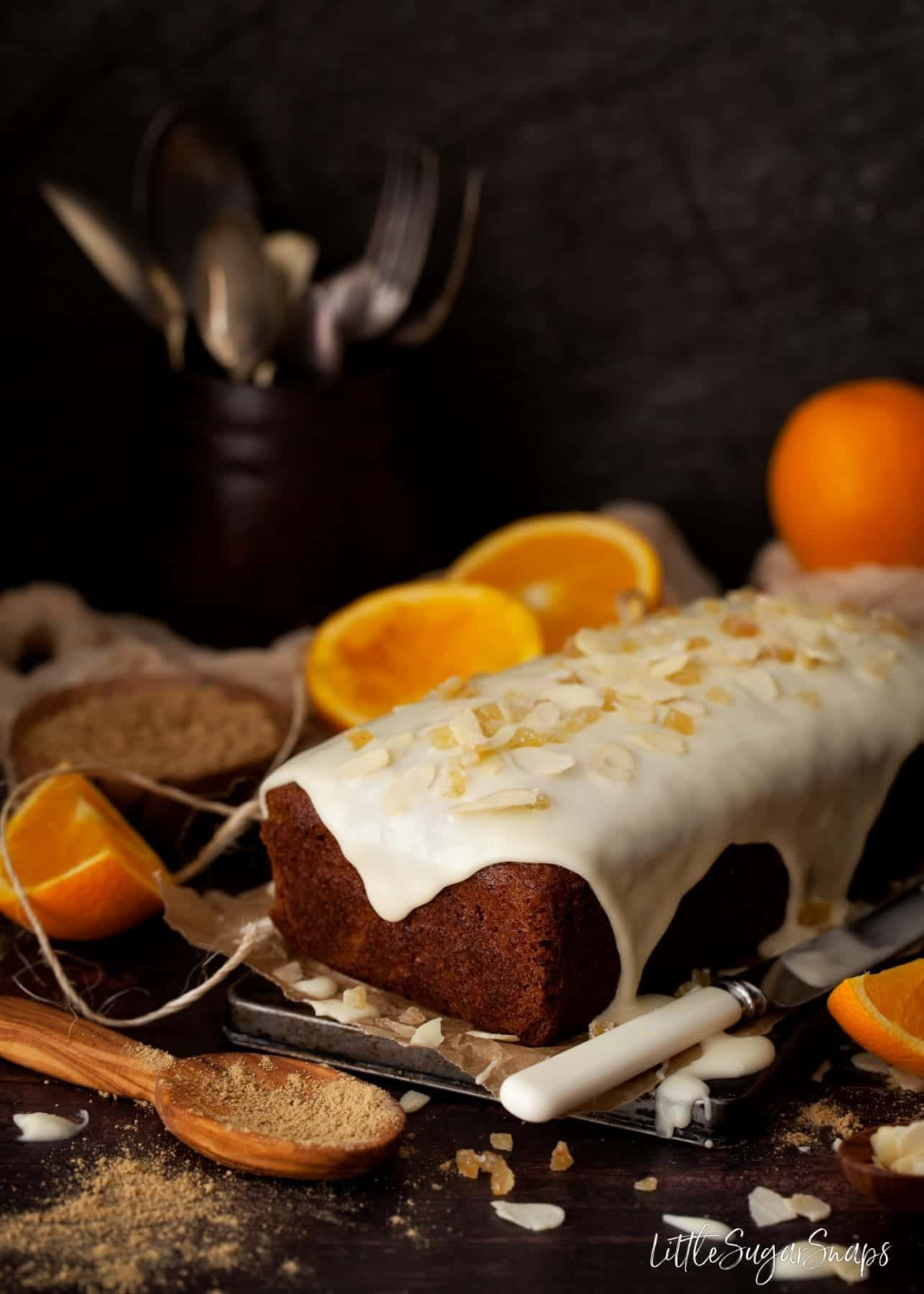 Vegan ginger cake with orange icing and crystalised ginger on top.