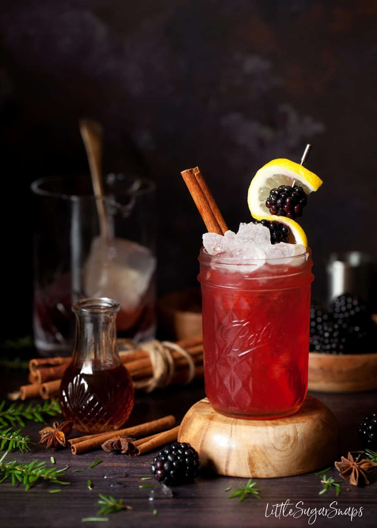 The Bramble Cocktail recipe decorated with lemon and blackberries with a cinnamon stick.