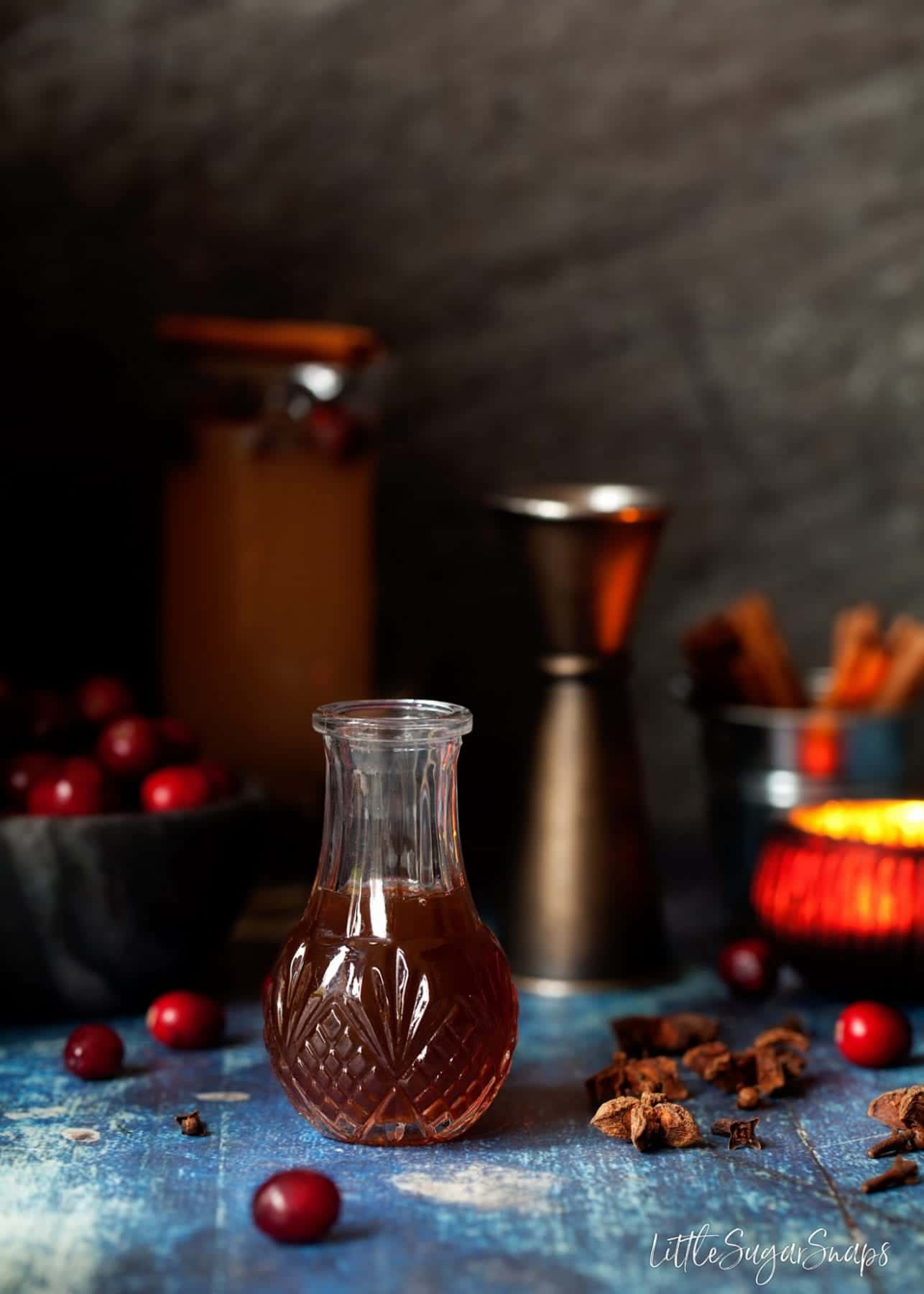 A small bottle of tonic syrup with cranberries, star anise and a tea light