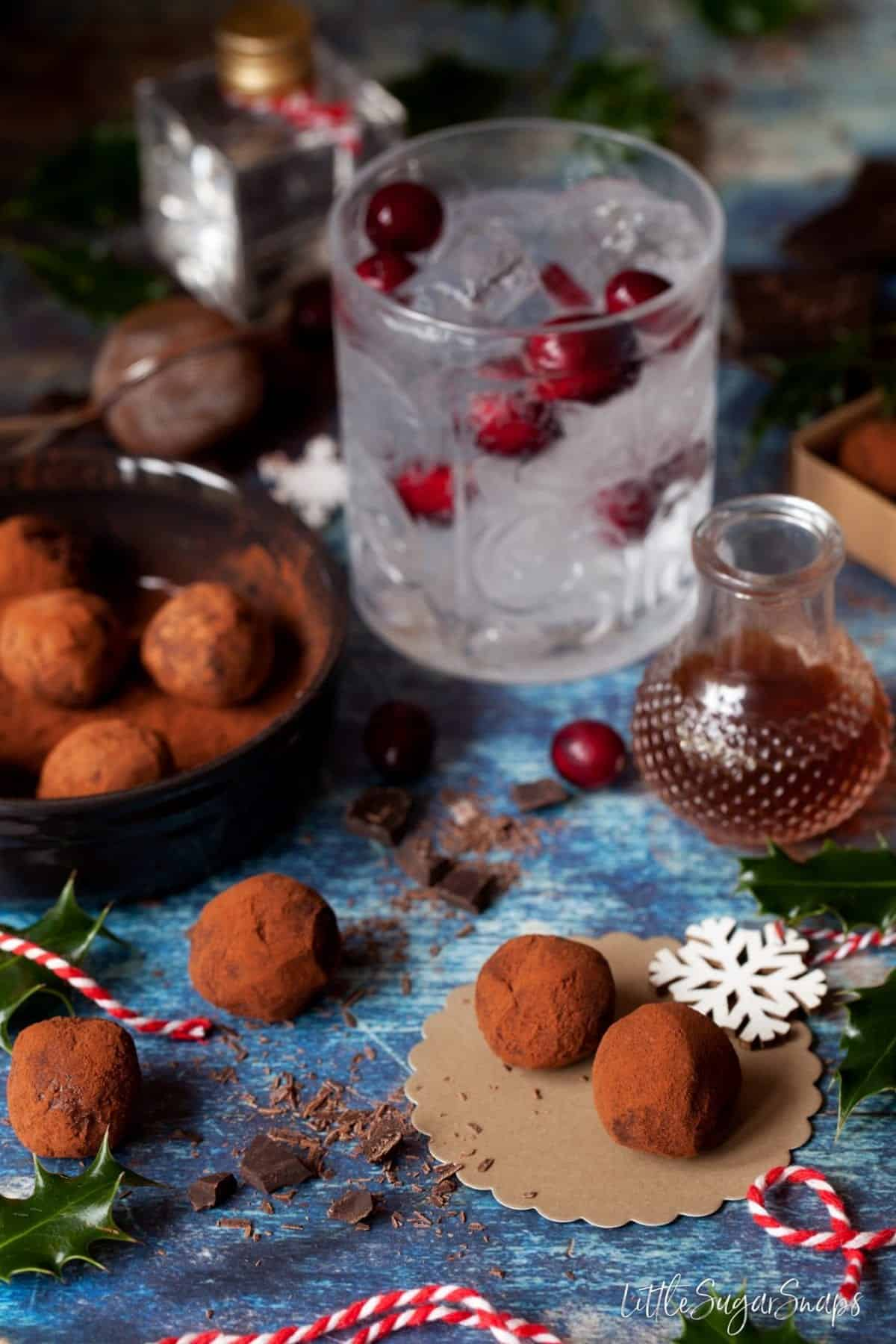 a gin and tonic with cranberries alongside a small bottle of tonic syrup and gin chocolates rolled in cocoa powder