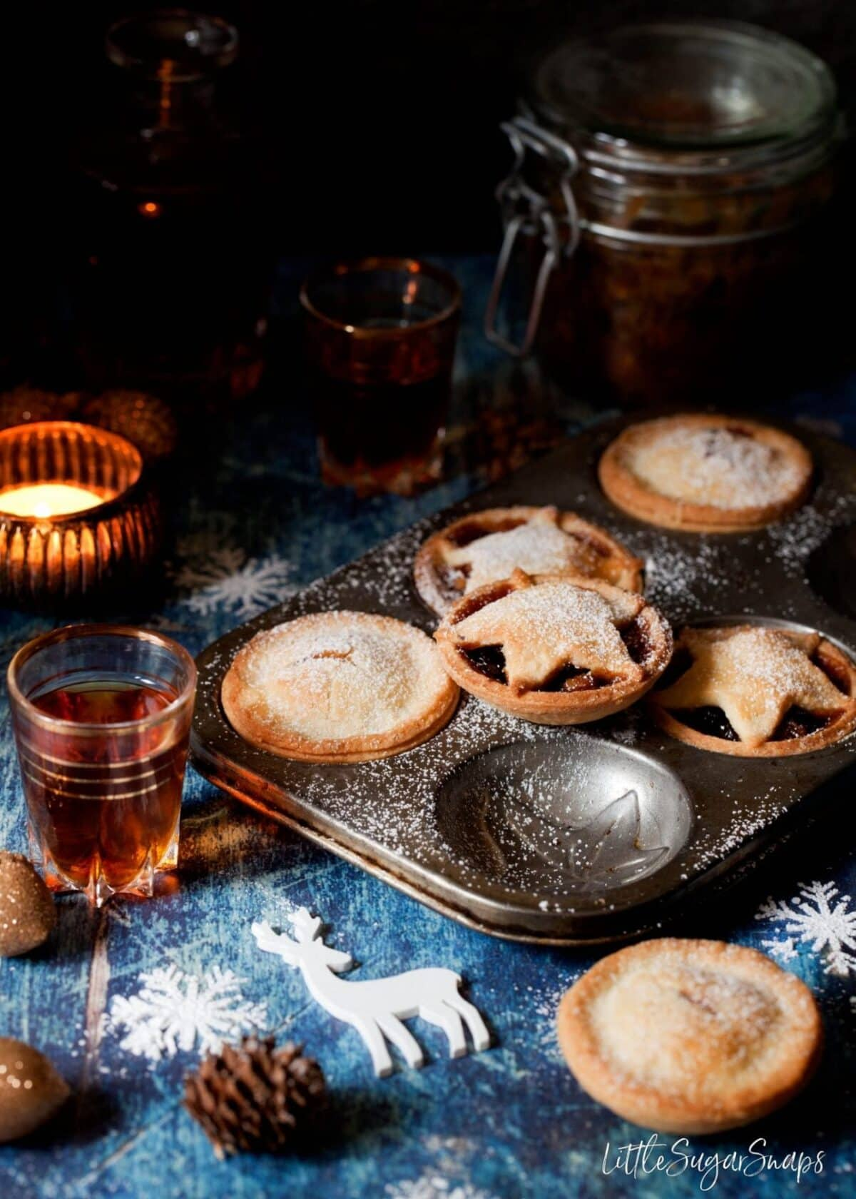 Gluten Free Mince Pies in a vintage baking tin with christmas ornaments and a glass of amaretto