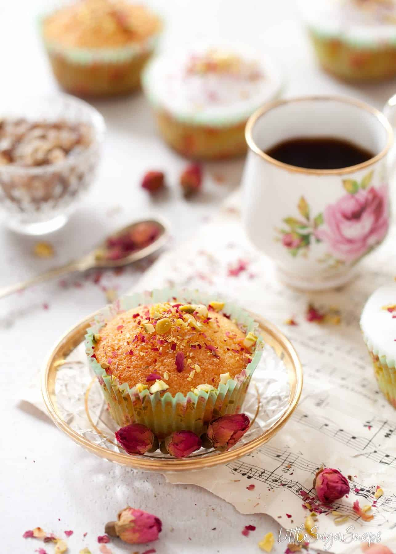 Persian Love Cupcake on a glass plate with a small coffee.
