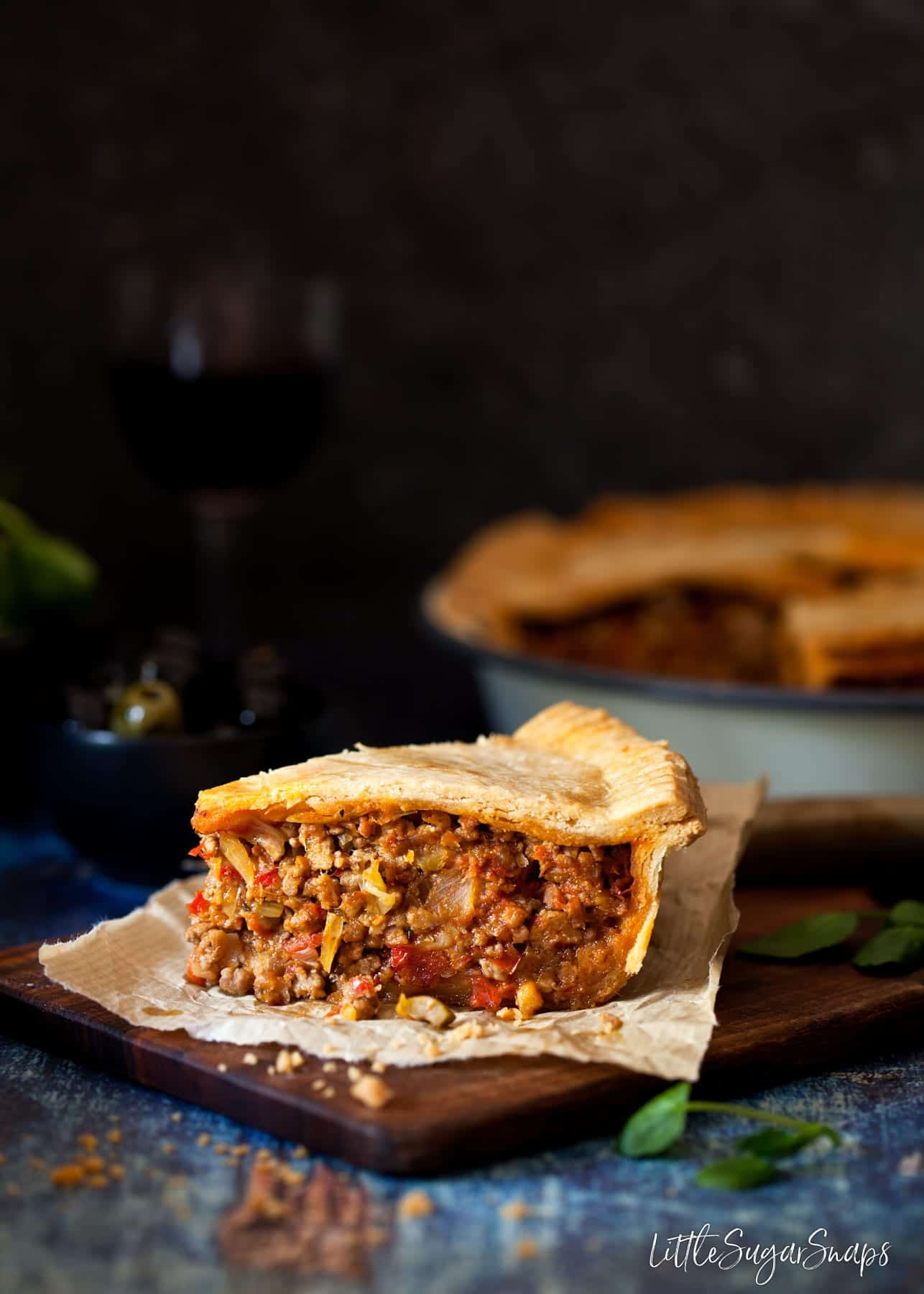 A slice of Mediterranean Lamb Pie on a wooden board.