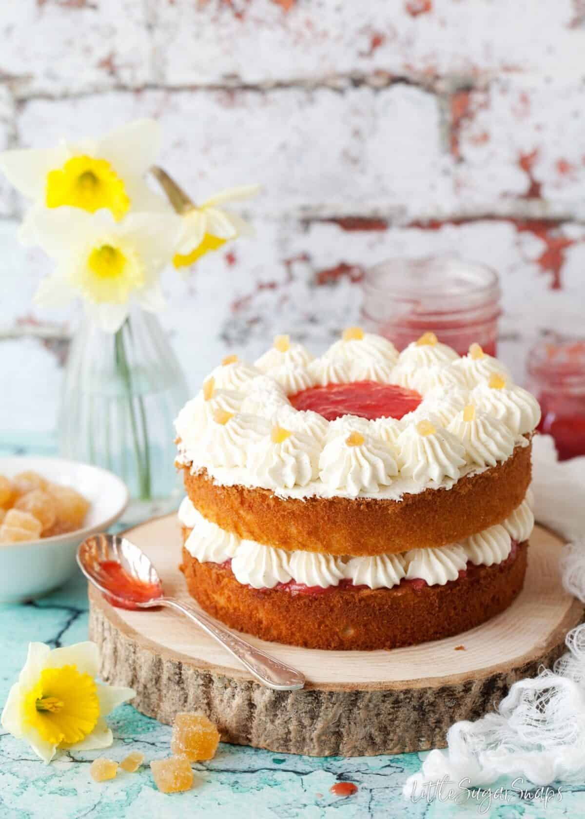 A vanilla sponge cake sandwiched with jam and whipped cream. Crystallised ginger and daffodils in shot. The cake is presented on a tree trunk style board