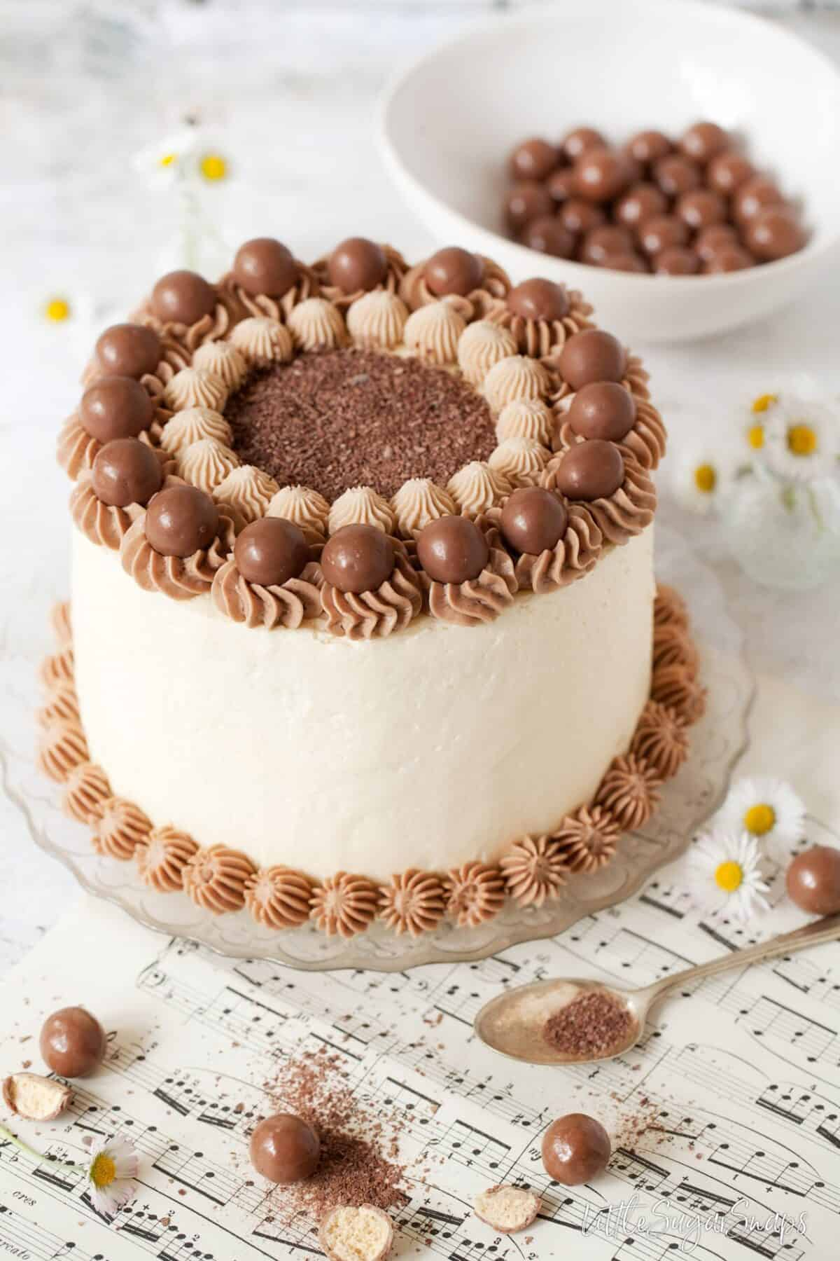 chocolate cake decorated with italian meringue buttercream and chocolate malt balls.