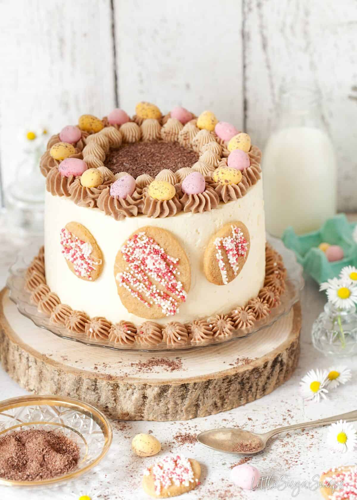 Layer cake decorated with mini eggs and egg shaped cookies.