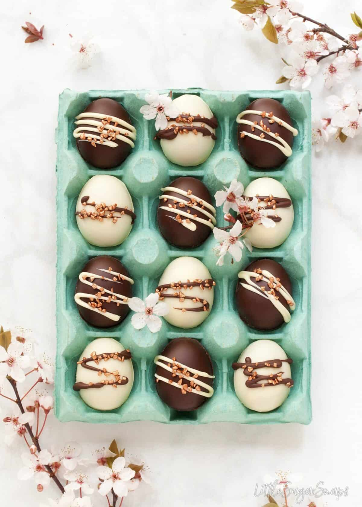 A box of chocolate easter eggs using a caramel shortbread recipe. Mix of white and dark chocolate eggs. decorated with contrasting chocolate stripes and bronze sprinkles