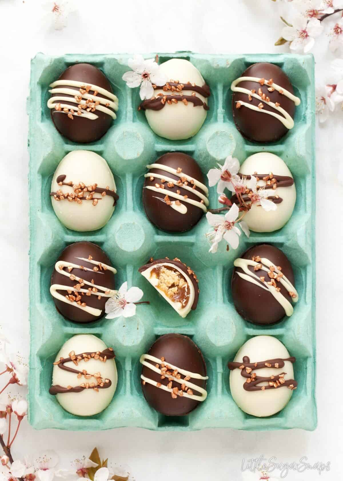 A blue egg box filled with chocolate caramel easter eggs made at home using and Easter egg recipe. Cherry blossom surrounding the eggbox