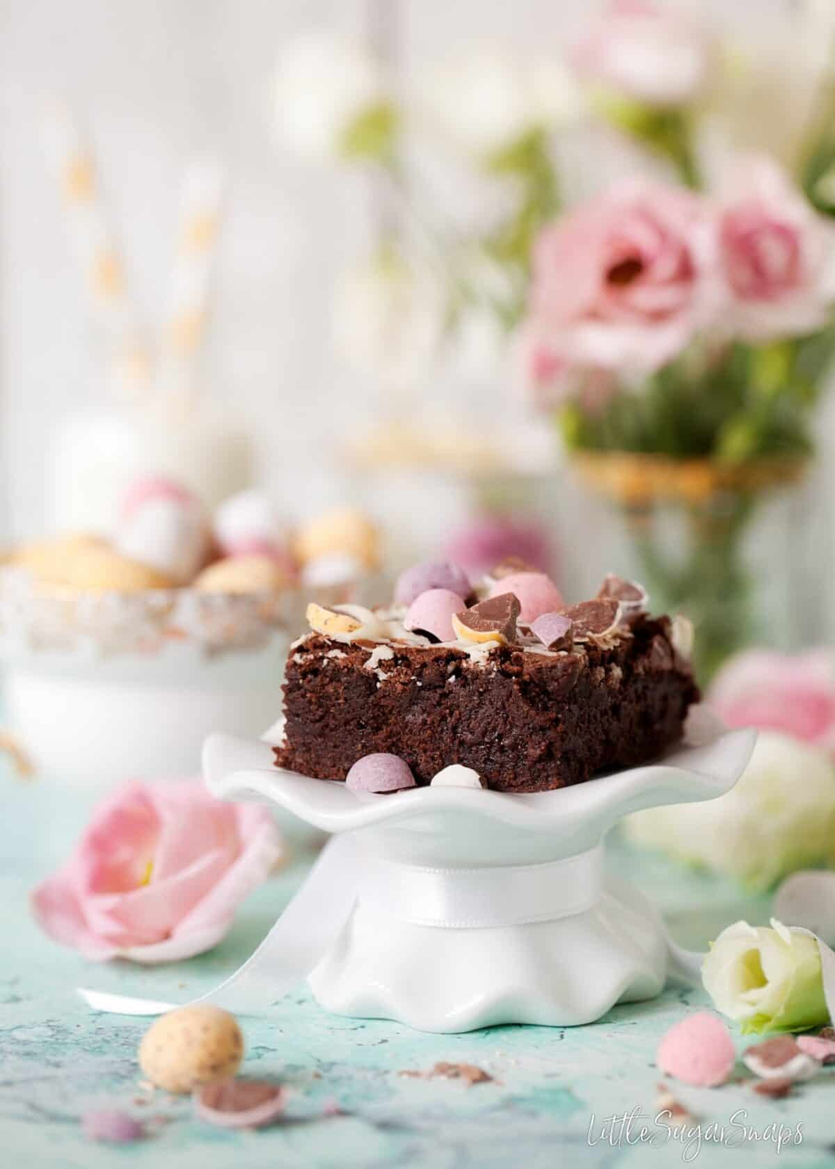 Mini Egg Brownie square on a small cake stand.
