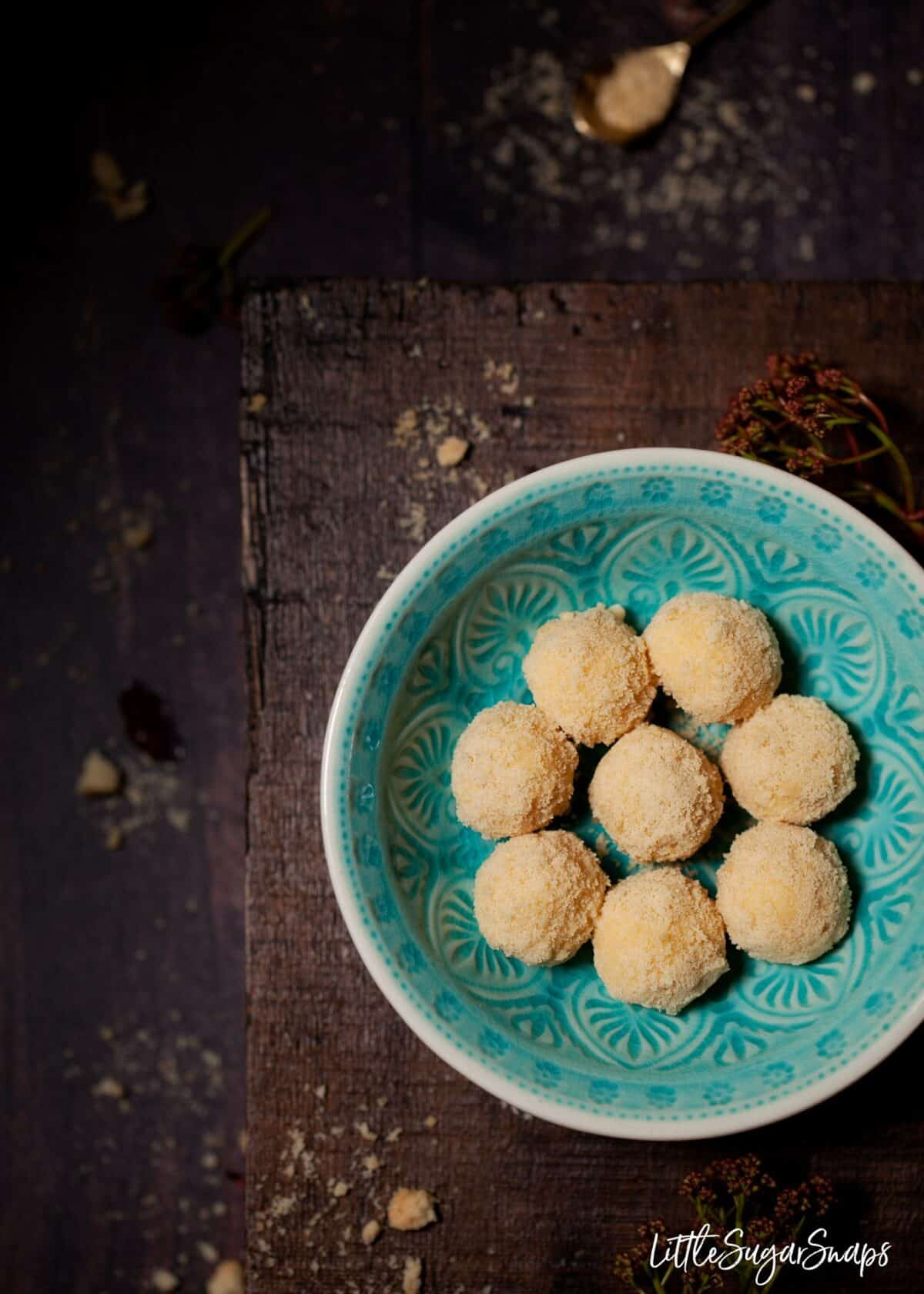 A blue bowl holding white chocolate truffles.