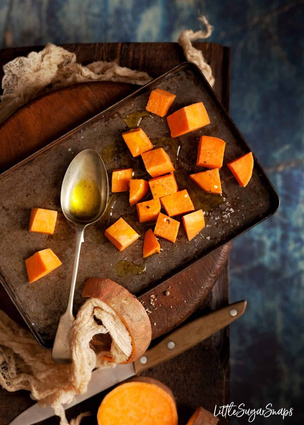 cubes of sweet potato on a baking sheet with olive oil