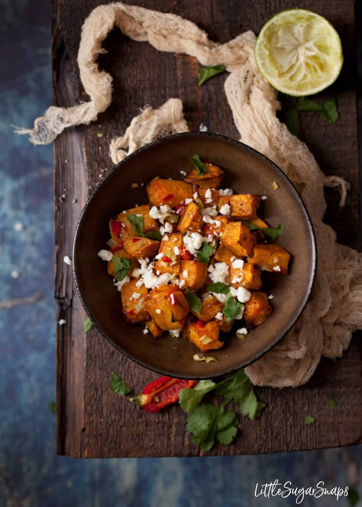 A bowl of roasted sweet potato cubes sprinkled with chilli, onion and feta