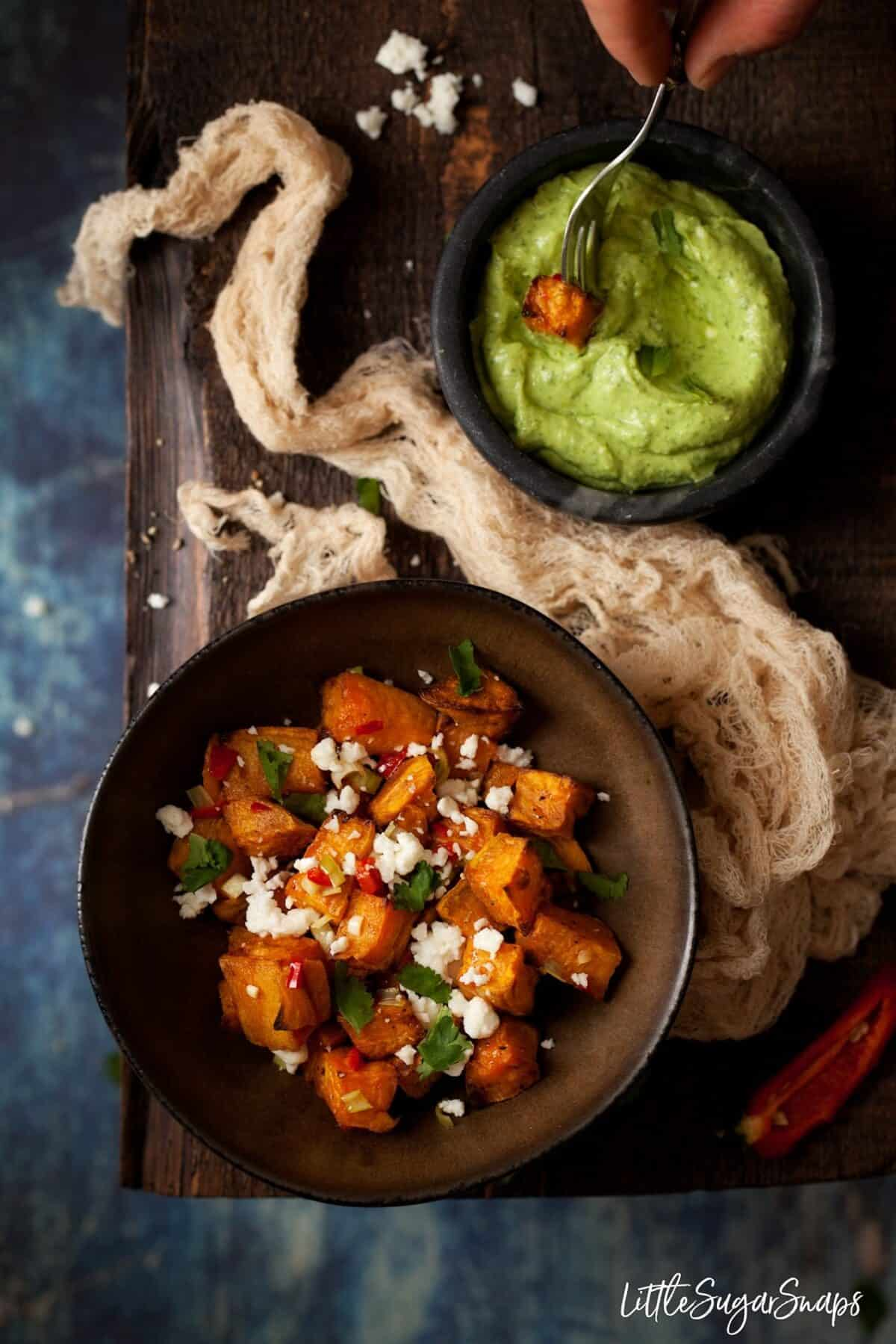 Chilli Feta sweet potatoes in a bowl with a cube being dipped in avocado and feta dip
