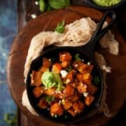 Chilli and feta sprinkled sweet potato cubes in small skillets with avocado feta dip