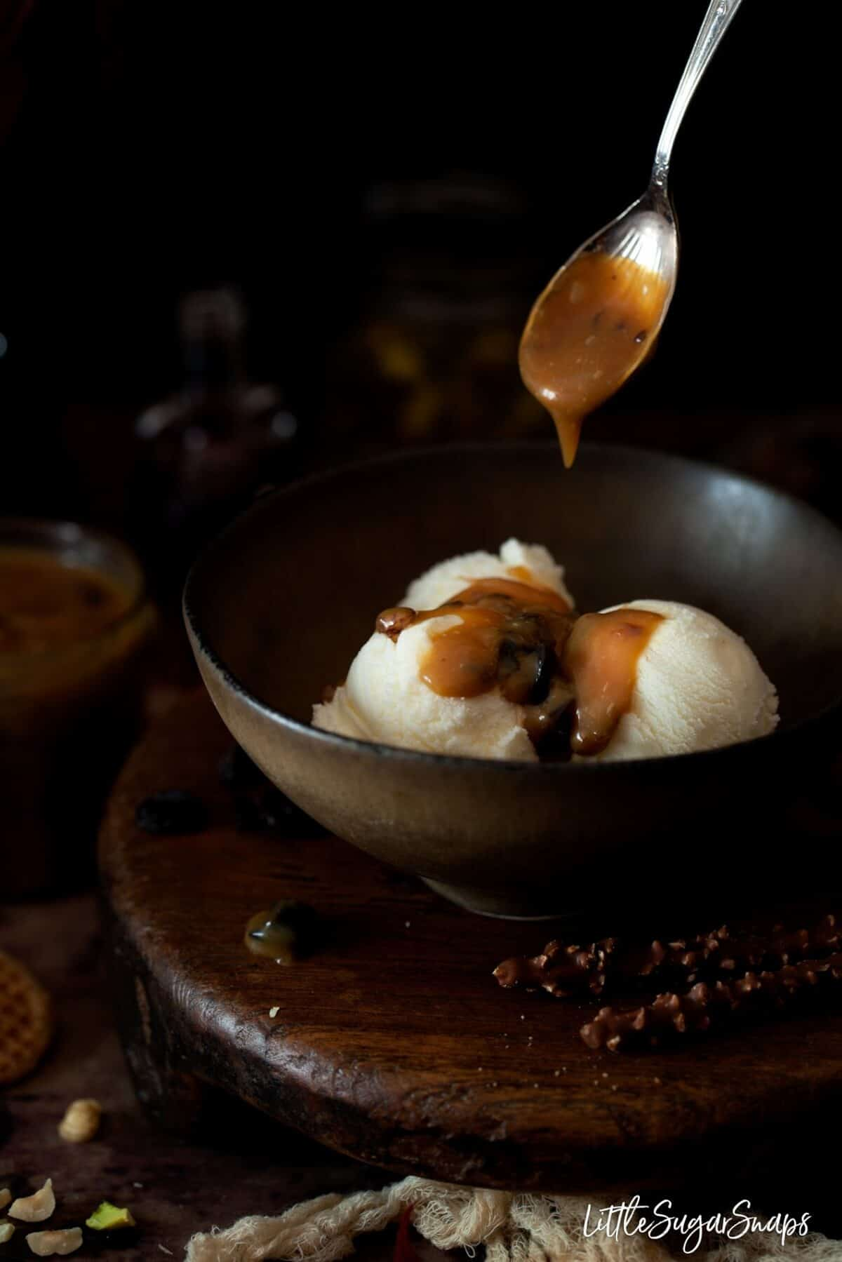 spooning rum & raisin caramel sauce onto vanilla ice cream in a bowl