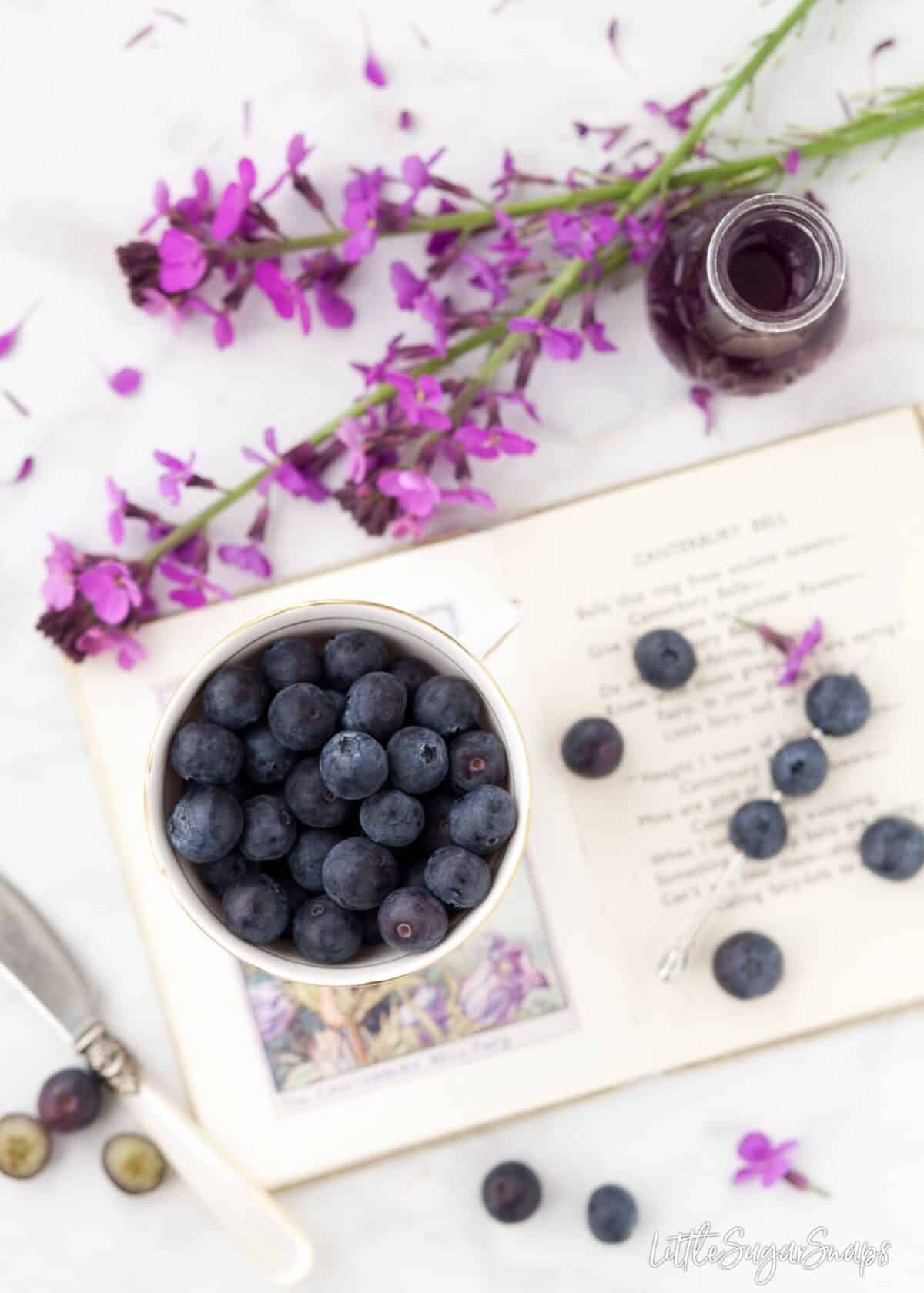 A bowl of blueberries with purple flowers