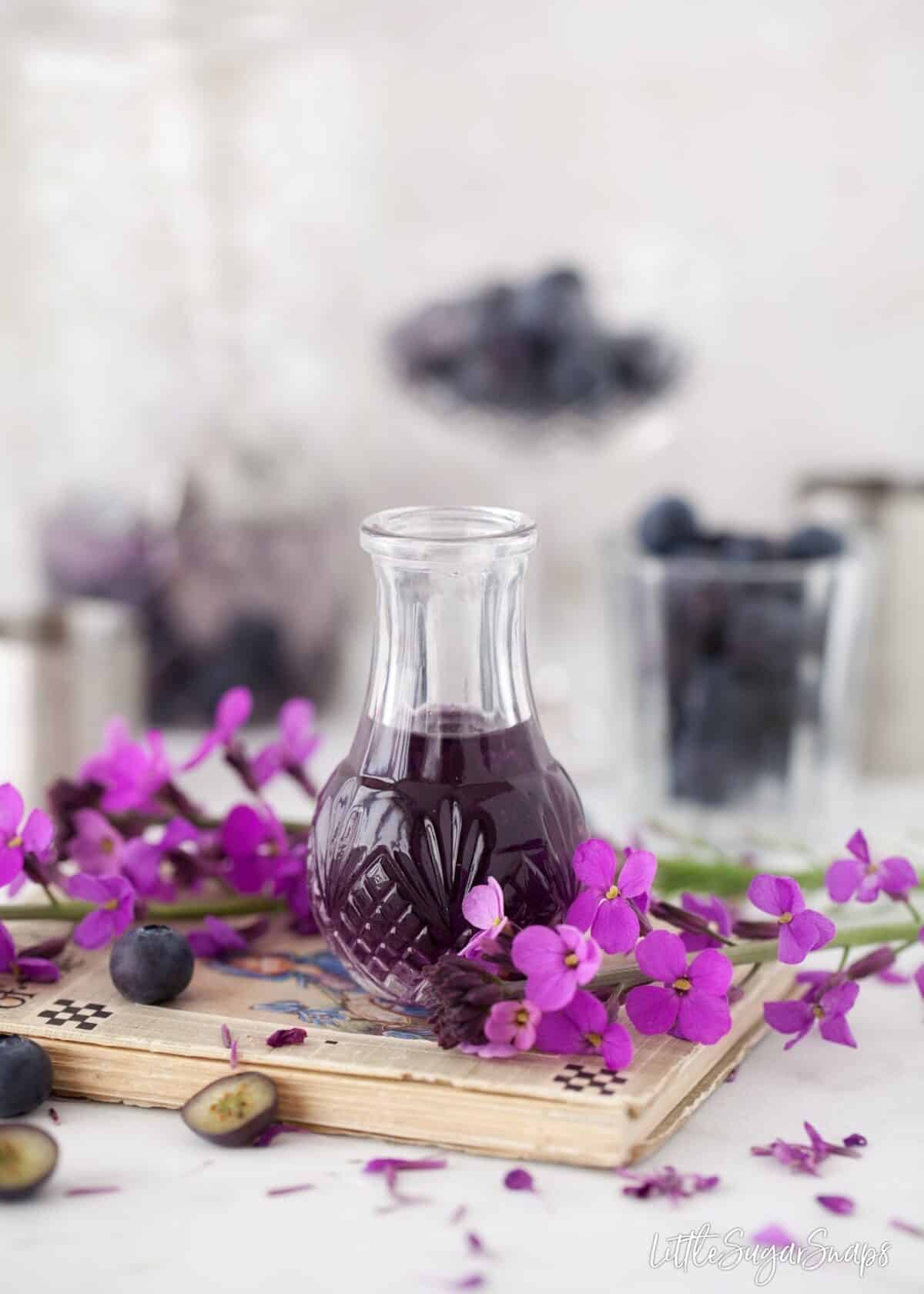 Violet liqueur with blueberries and purple flowers