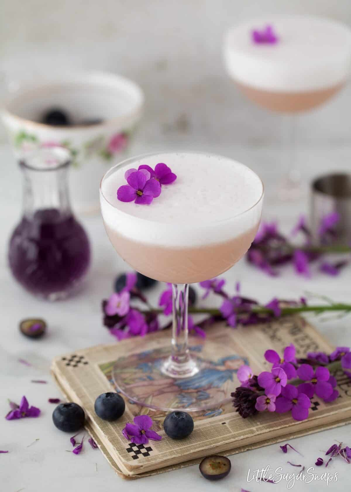 Violet Blueberry Gin Sour decorated with flowers