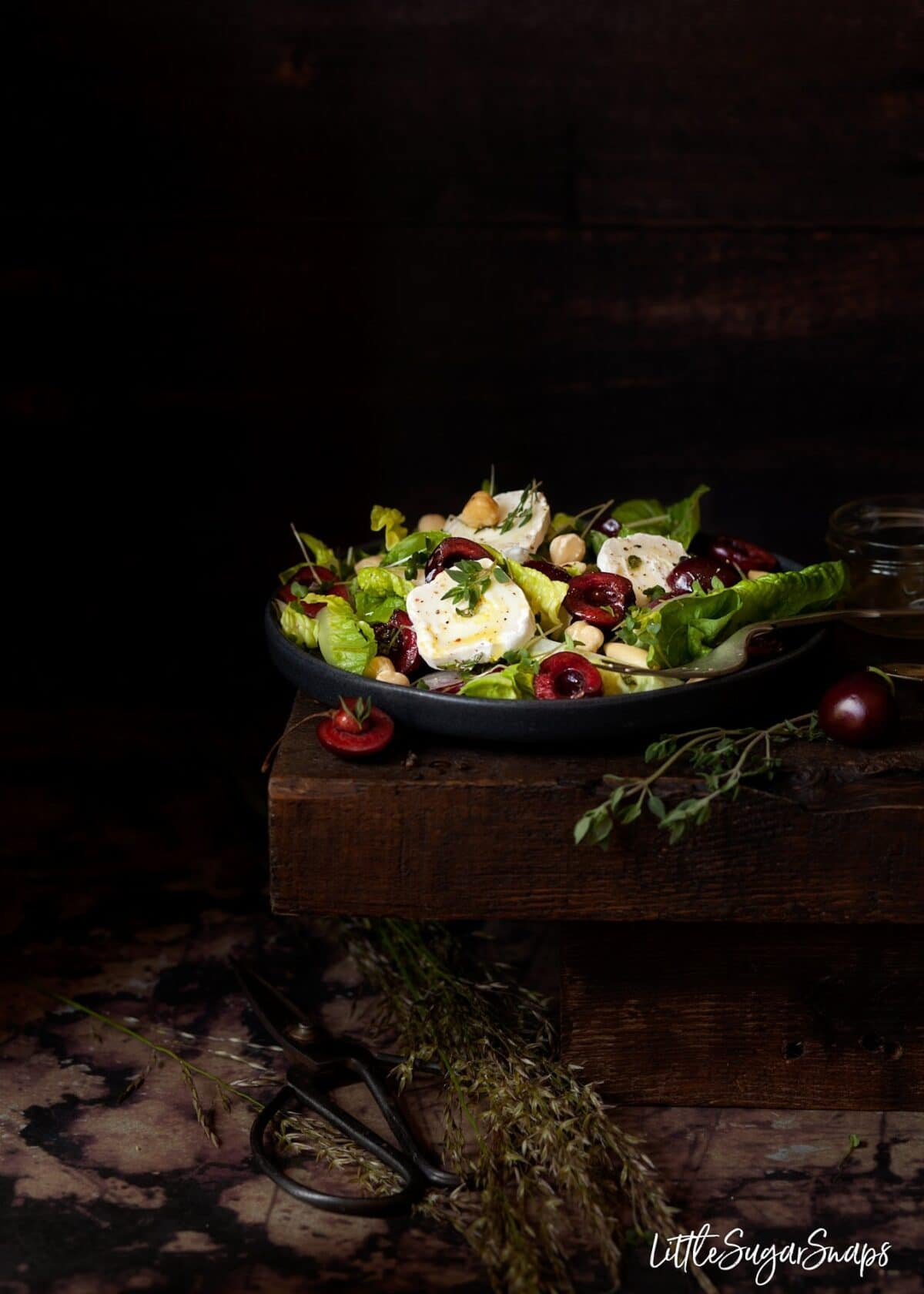A plate of salad leaves with fresh cherries, goats cheese and thyme.