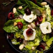 A Plate of Cherry and Goats Cheese Salad with honey dressing, radish and nuts