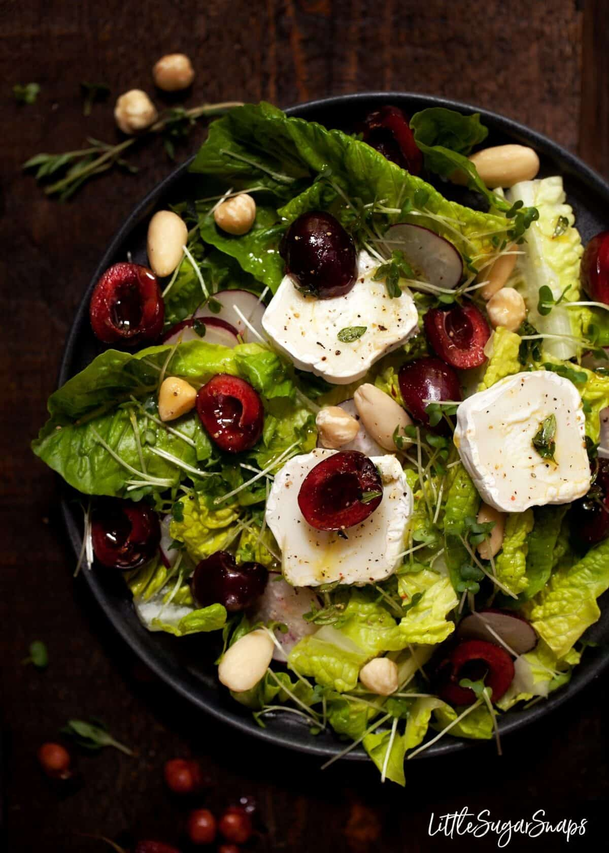Close up view of Cherry & Goats Cheese Salad with hazelnuts, almonds & honey dressing