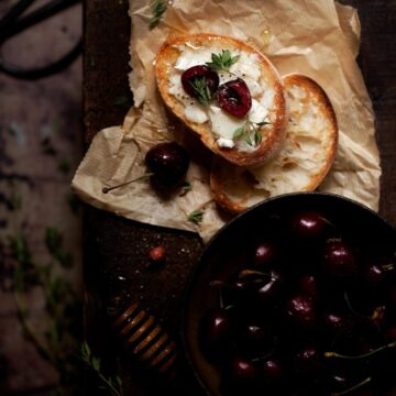 Cherry and Goats Cheese Crostini with honey drizzle on a bench