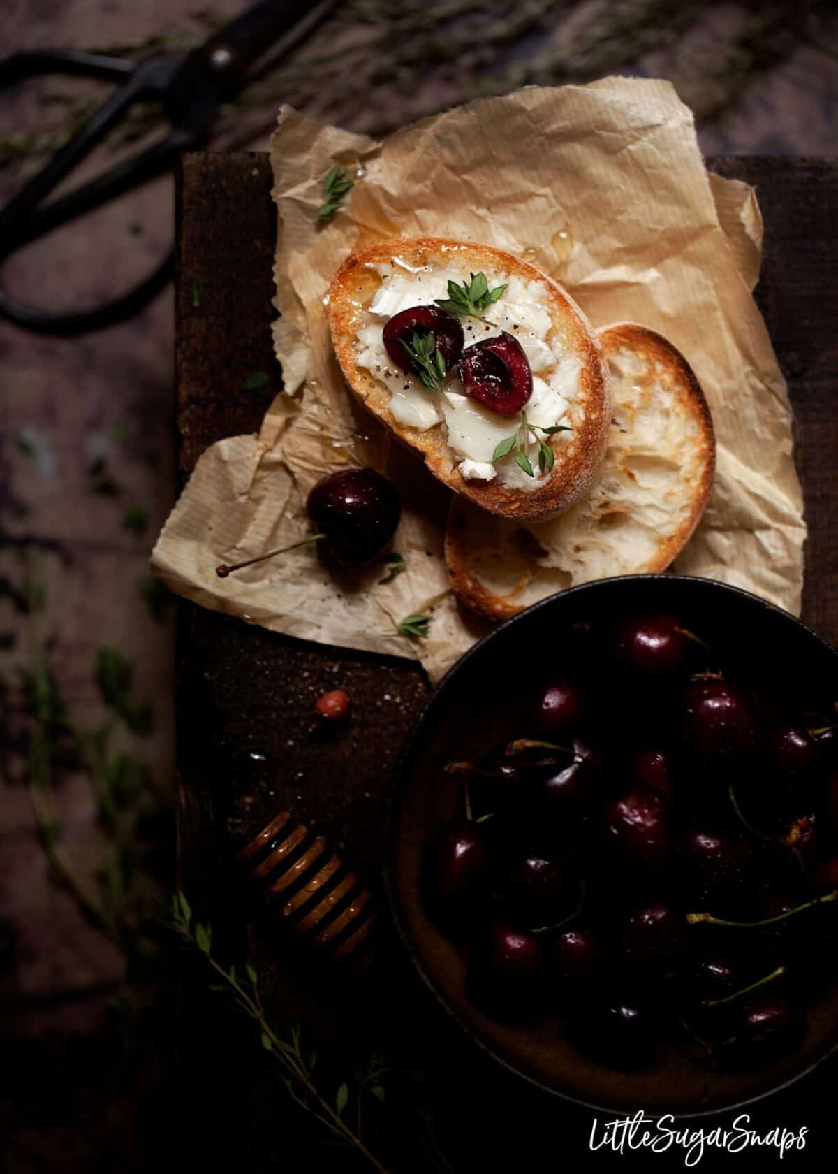 Simple crostini with goats cheese, cherries and honey net to a bowl of cherries