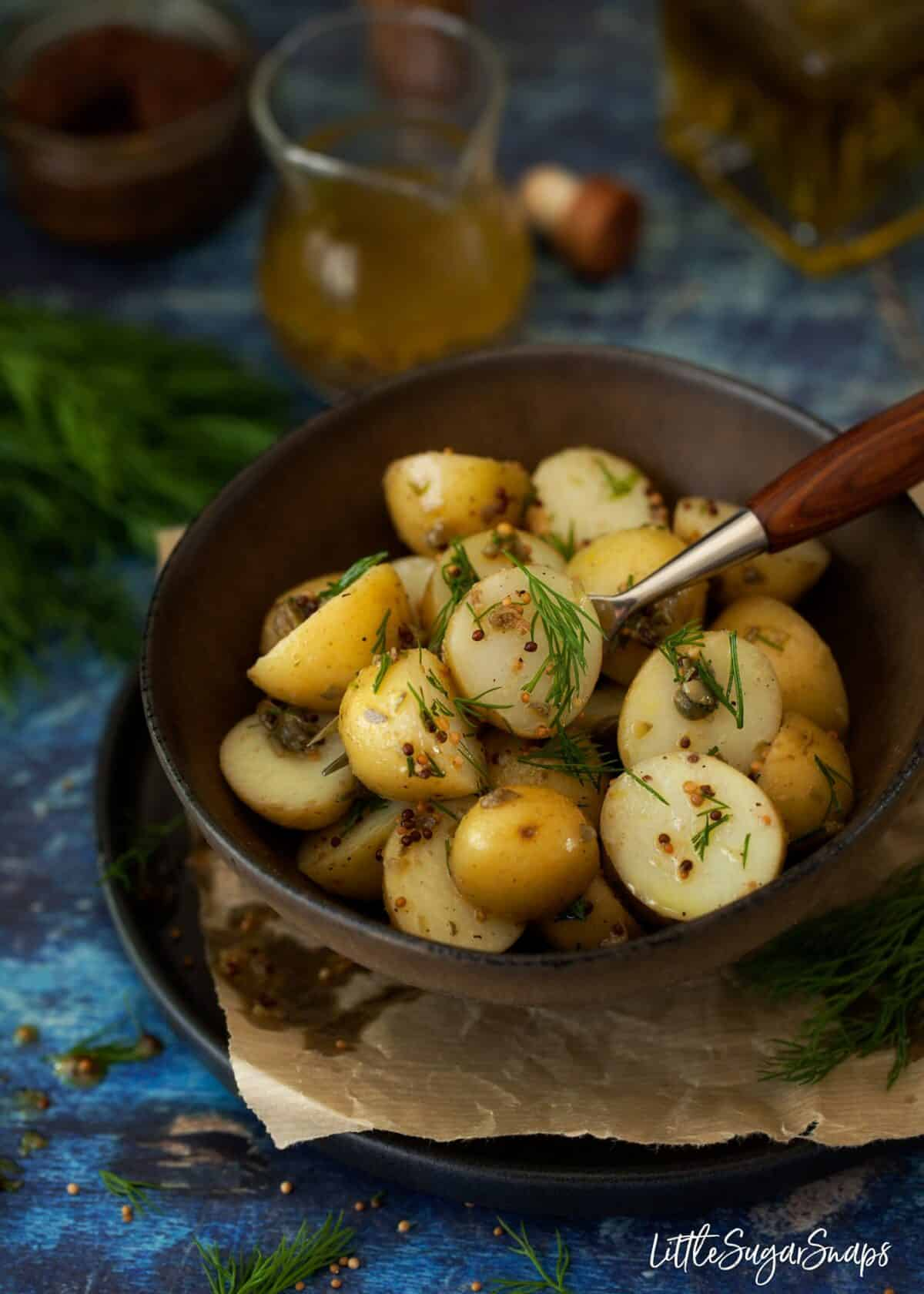 A bowl of potato salad with mustard vinaigrette and dill