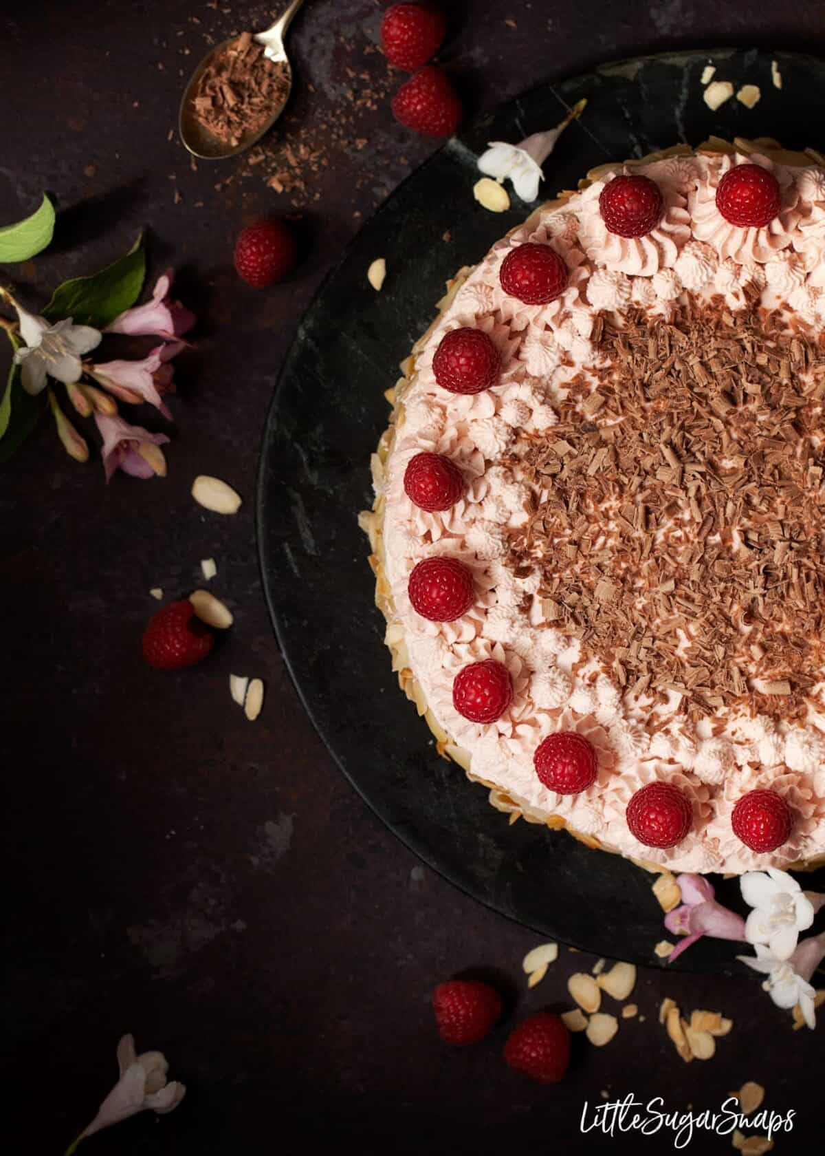 Topview of a raspberry gateau with piping cream, fresh raspberries and chocolate.