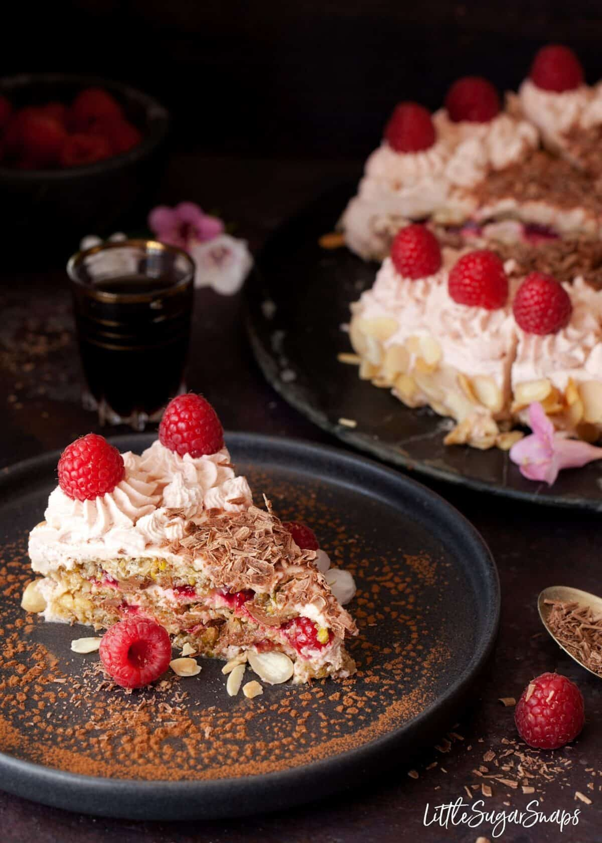 A slice Chocolate Raspberry Dacquoise Cake on a black plate, in front of the entire cake it was cut from. Layers of meringue, cream and raspberry coulis are evidentand the slice is topped with fresh fruit and chocolate flakes