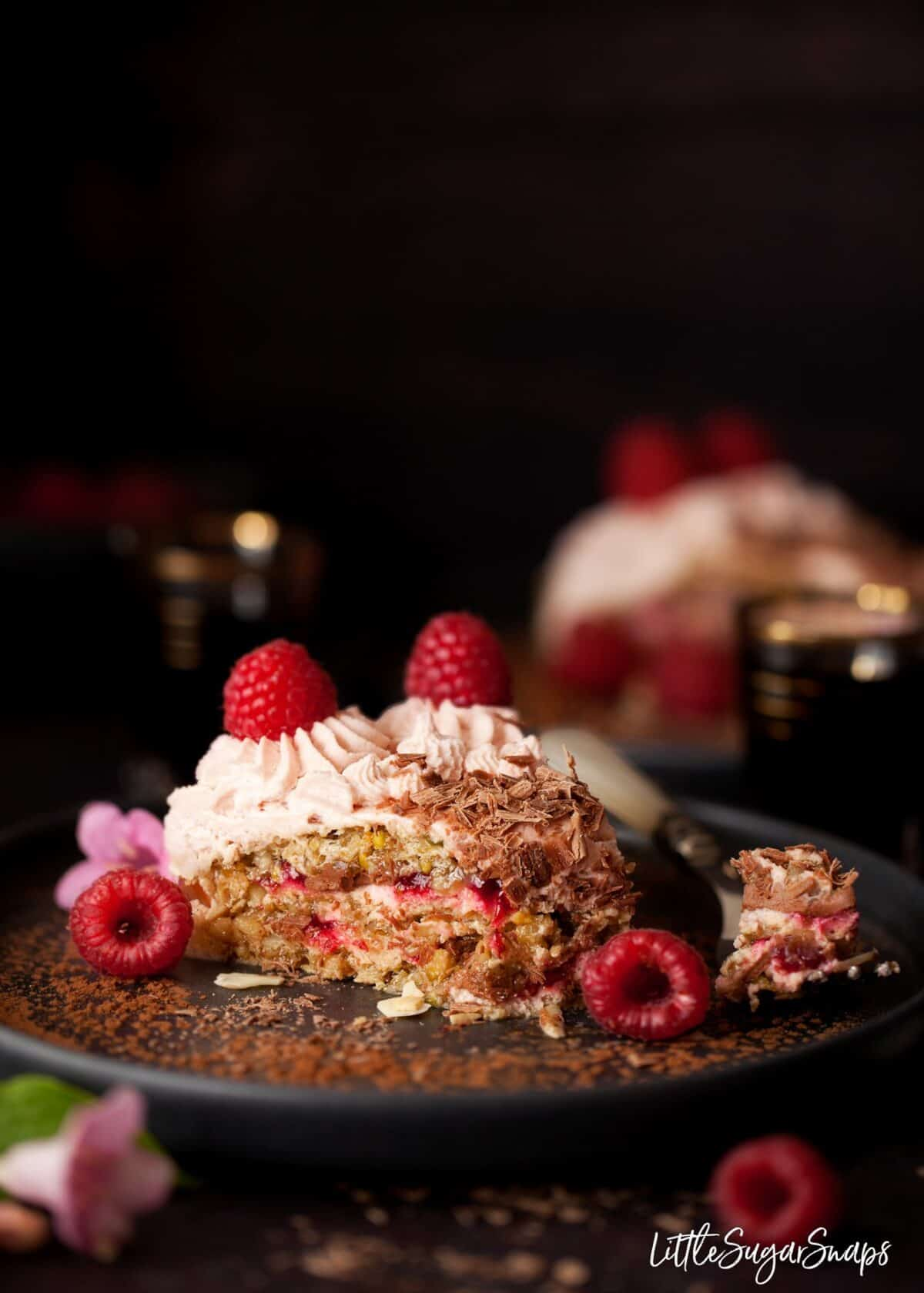 A slice of chocolate raspberry dacquoise cake on a black plate