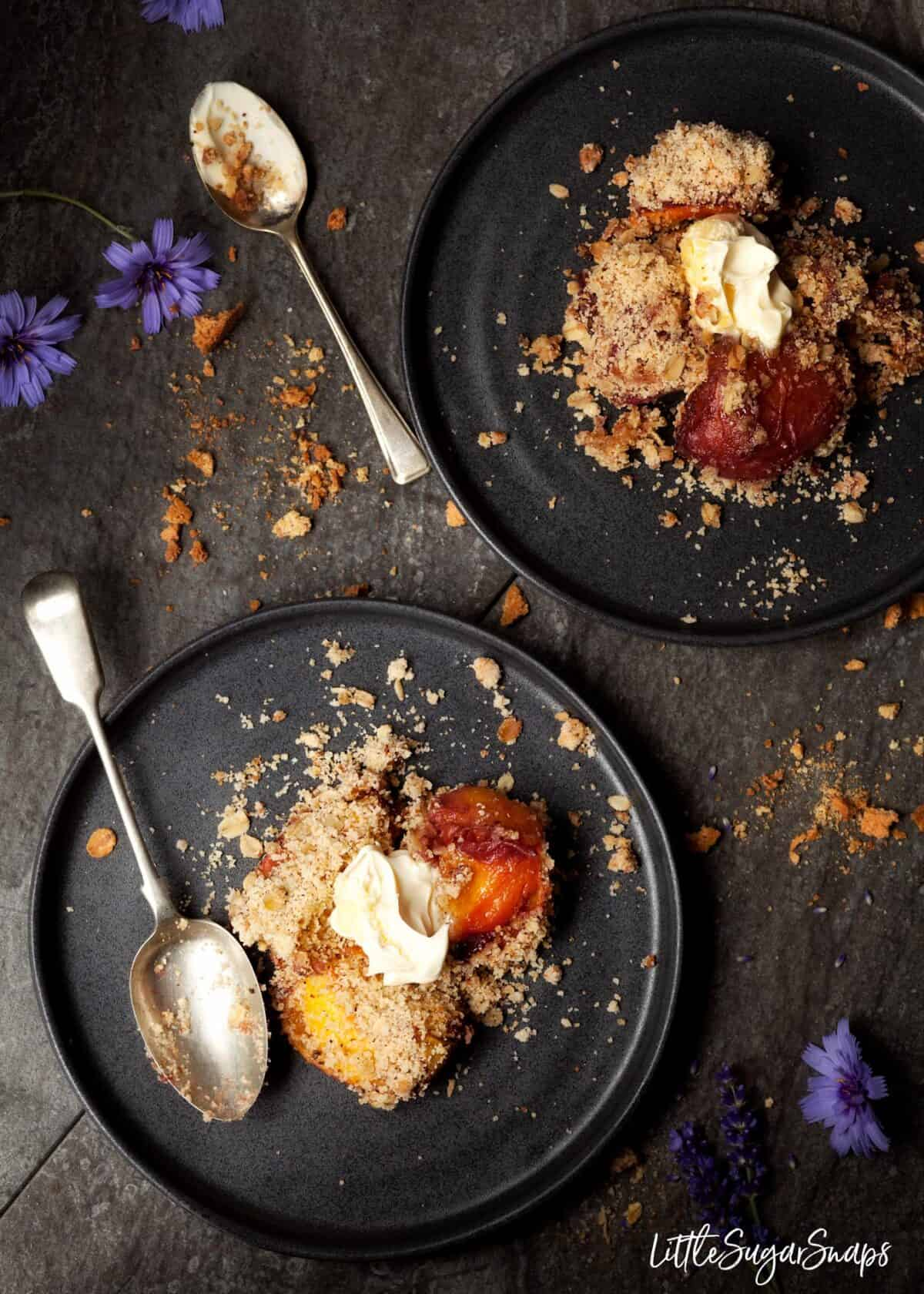 Two plates of peach crumble with clotted cream