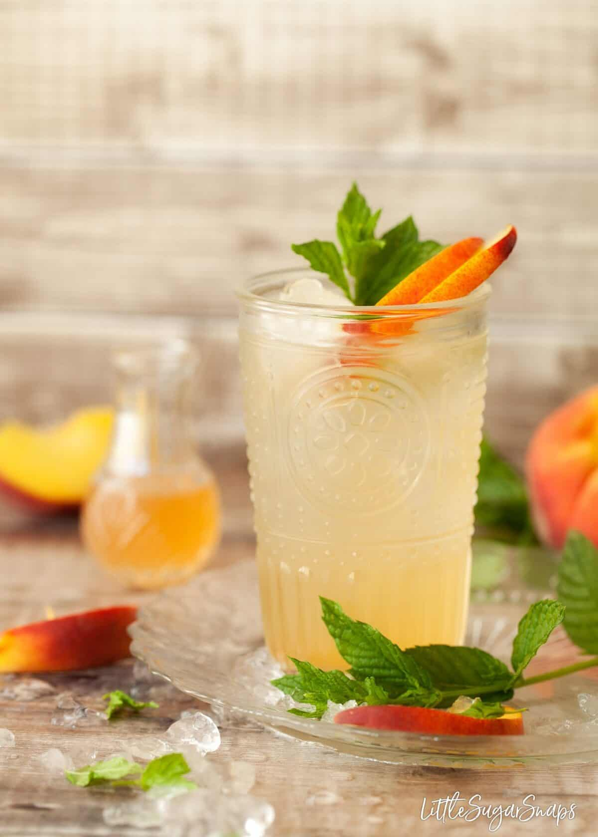a glass of peach syrup topped up with water with fresh peach and mint