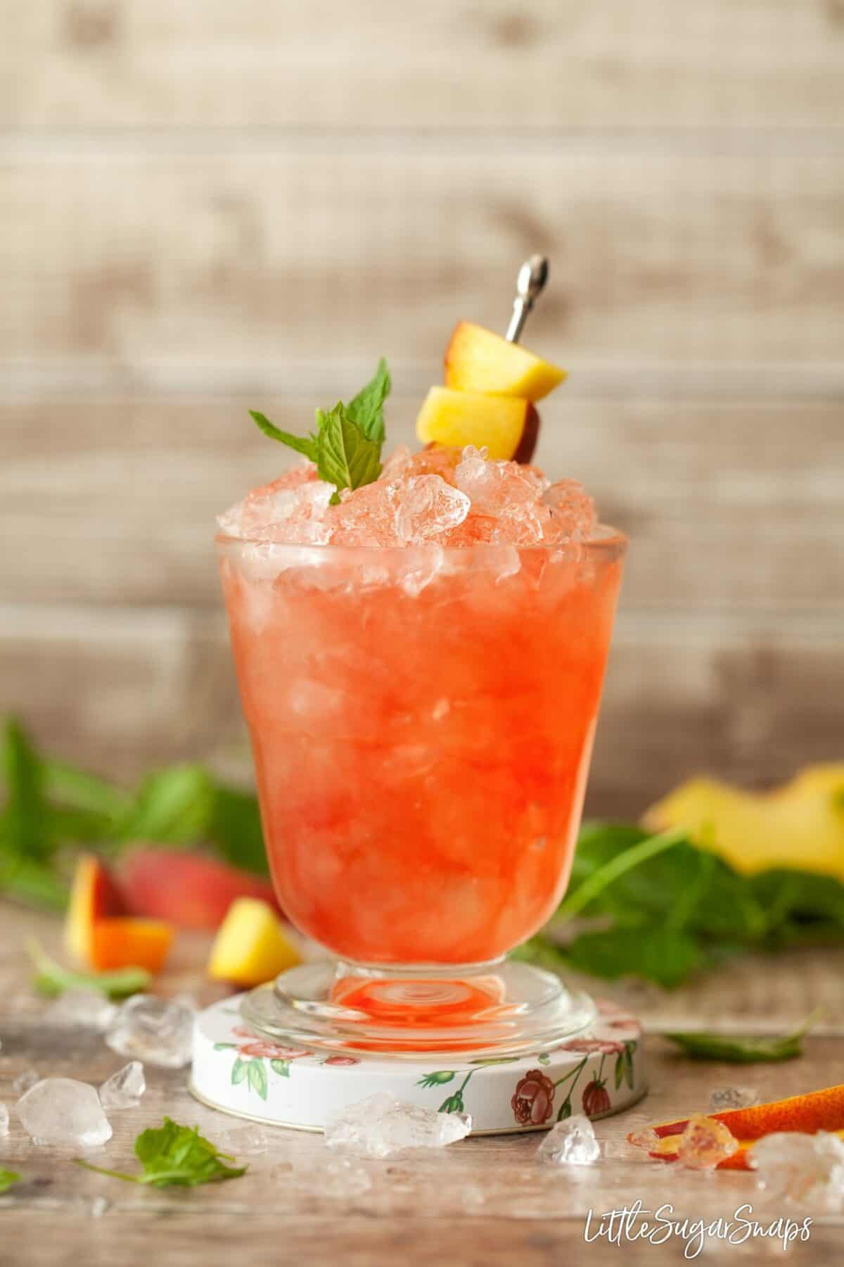 Close up of a raspberry peach bramble cocktail