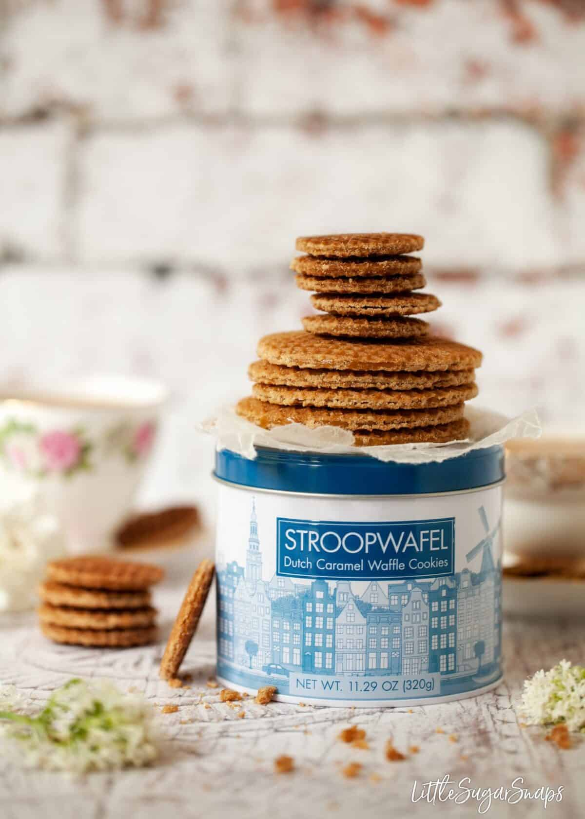 A stack of full size and mini caramel waffle cookies on a cookie tin