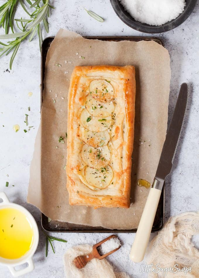 a cheesy potato tart on a baking sheet with rosemary, sea salt, olive oil and a knife for slicing