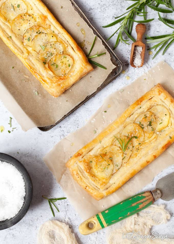 two brie and potato tarts with rosemary and sea salt. Both on baking parchment with ingredients in bowls and around the edges of the image