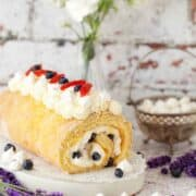 lemon Meringue Swiss Roll with summer berries on a worktop there are pieces of meringue, blueberries and lavender in shot