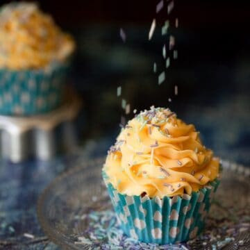 Cupcakes topped with piped French buttercream with sprinkles being scattered on top. The cake in in a bright blue wrapper with polka dots