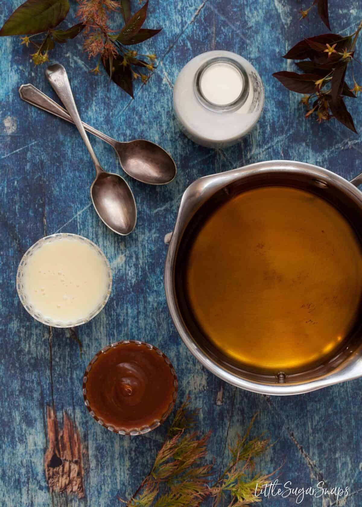 borubon in a pan ready to be mixed with cream, condensed milk and caramel sauce with vintage spoons on a blue surface