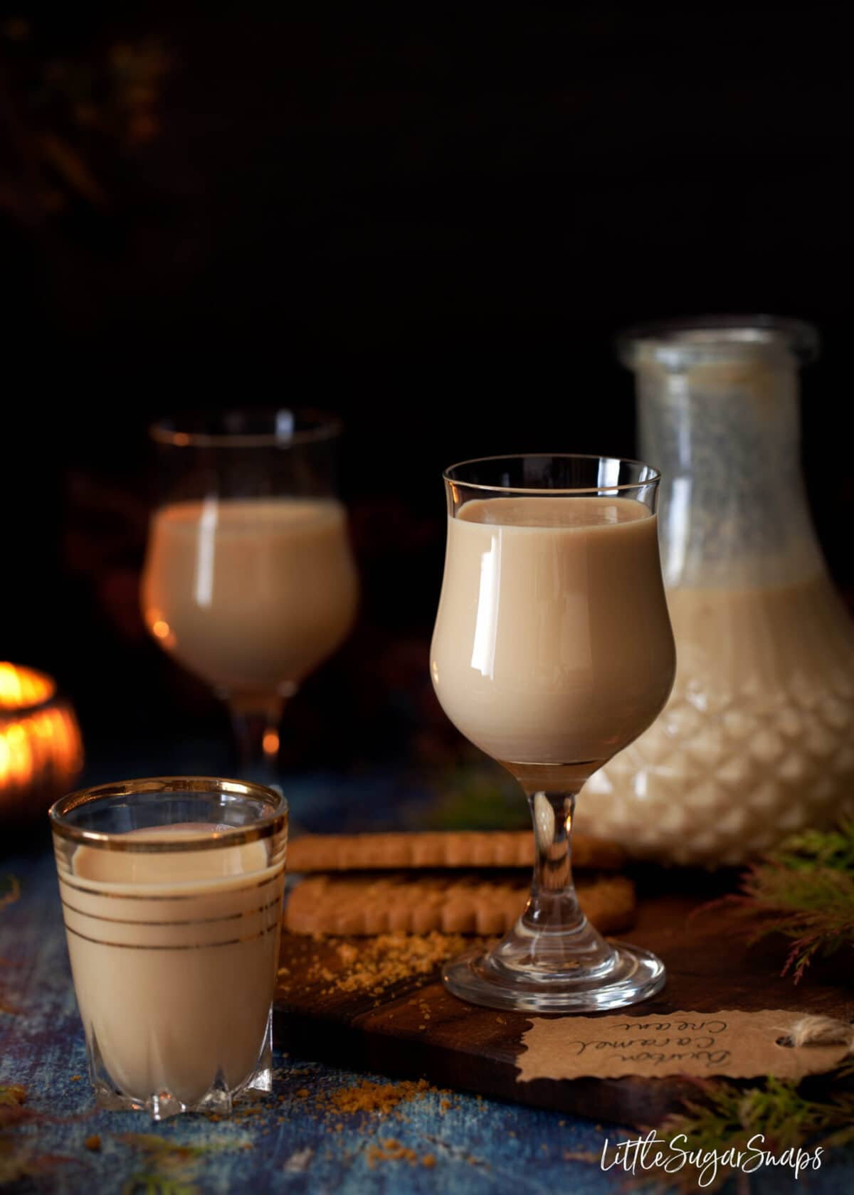 glasses of caramel bourbon cream liqueur poured - stem glasses and shot glasses on a wooden board with biscoff cookies