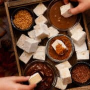 A tray filled with pumpkin spice marshmallow chunks, chocolate sauce, caramel sauce, crushed cookies, bronze sprinkles and caramel curls. Children are dipping some of the marshmallow into the sauces