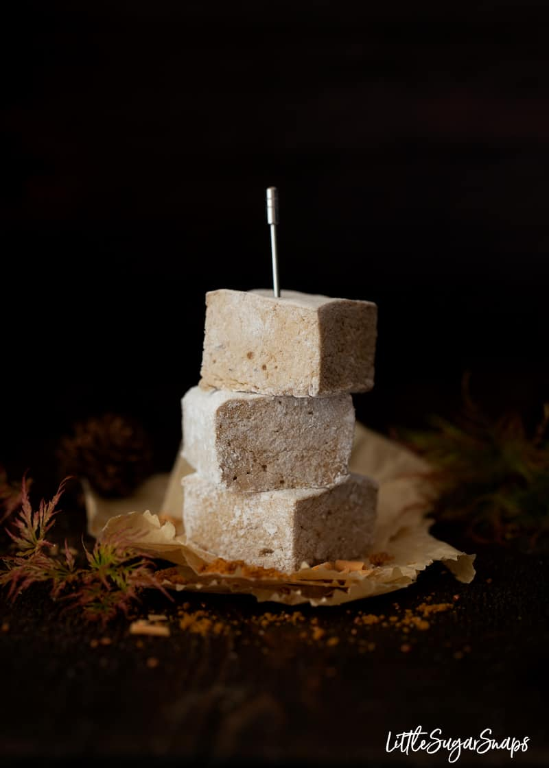 A stack of 3 cubes of homemade marshmallow on greaseproof paper with autumn foliage around it. Held in place with a cocktail pick