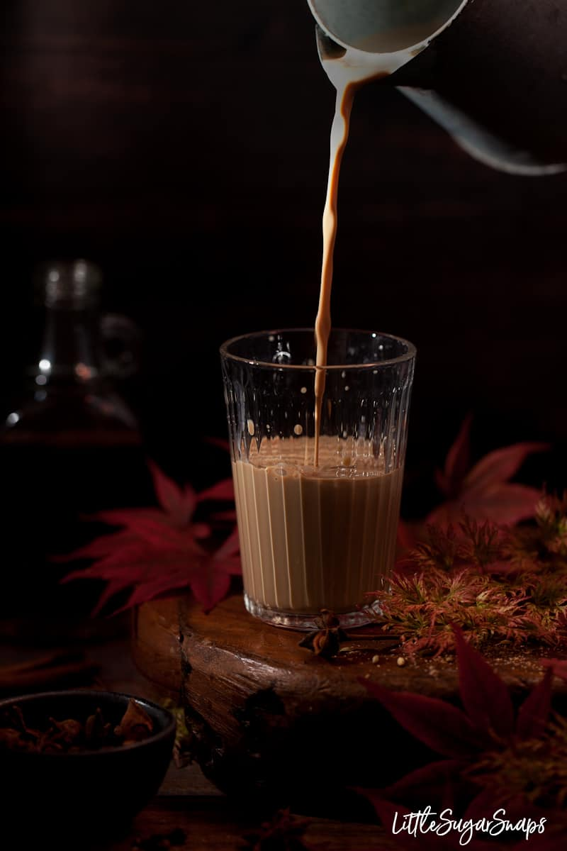 Rum masala chai being poured into a glass with spices and red leaves alongide. Bottle of rum in the background