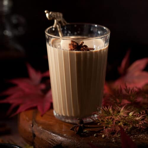 Glass of masala chai garnished with star anise