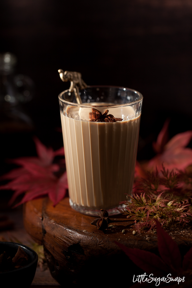 A glass of rum masala chia on a wooden stand with star anise garnish